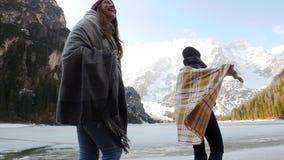 在毯子盖的两旅行的年轻女人走在冻湖的海岸 股票录像