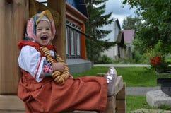 在民间卡夫坦长衣打扮的小美女吃百吉卷在井附近 免版税库存照片