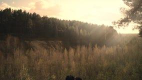 在民间服装的年轻夫妇坐俯视森林的岩石 股票视频