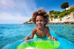 在气垫的非洲男孩游泳在海 免版税库存照片