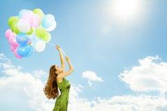 在气球的妇女飞行,有五颜六色的气球的愉快的女孩 图库摄影