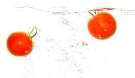 在水下的两个蕃茄在白色背景 免版税库存图片