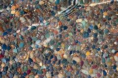 在水下的小卵石岩石与波浪和有些泡影 免版税库存图片