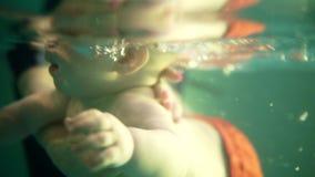 在水下的第一下潜 母亲或教练员教婴孩游泳在水下 然后举行在水下 股票录像