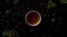 在水下落的莓果用樱桃,绿色葡萄,橙色切片,石灰,柠檬切片 免版税库存照片