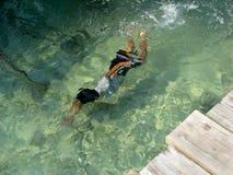 在水之下的儿童游泳 库存照片