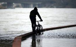 在水位高以后的被充斥的自行车道路在河 库存图片