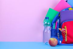在水和苹果旁边教育有办公用品的背包在桃红色和蓝色背景 免版税图库摄影