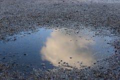 在水坑反射石渣的云彩 免版税库存图片