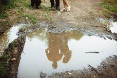 在水坑反映的人们 免版税库存照片