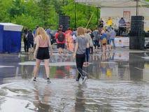 在水坑的两个女孩步行 免版税图库摄影