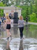 在水坑的两个女孩步行 图库摄影