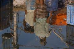 在水坑的反射 捕鱼港口的雇员被反射水的表面上 库存图片