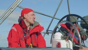 在水手早晨四至八时的守望期间的驾游艇者在游艇航行驾驶舱内在海洋 股票视频