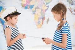 在水手镶边衬衣措施距离的两个美丽的孩子在与测量的磁带的世界地图 库存照片
