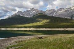 在水旁边的野餐桌与在距离的山 库存照片