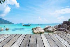 在水晶海的木板条灰色有长尾巴小船的 库存图片