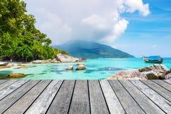 在水晶海的木板条灰色有长尾巴小船的 图库摄影