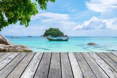 在水晶海的木板条灰色有长尾巴小船的 免版税库存照片