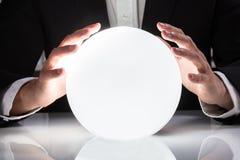 在水晶球的商人手 免版税库存照片