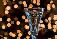 在水晶长笛的香宾反对圣诞树点燃 免版税图库摄影