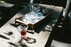 在水杯的热的滴水咖啡在与苛刻的阳光的木桌上 免版税库存图片