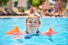在水池的女孩游泳在臂章在一个热的夏日 免版税库存图片