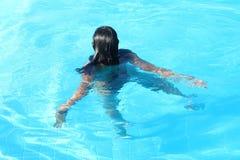 在水池的年轻女人游泳 免版税库存照片