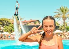 在水池的微笑的青少年的女孩enjoing的暑假与飞行在背景的板watershow 免版税图库摄影