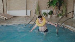 在水池的快乐的人游泳与可膨胀的圈子 影视素材