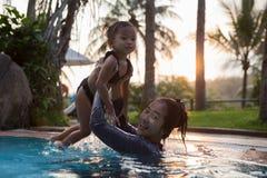 在水池的母亲和女儿游泳 库存照片