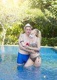 在水池的爱恋的夫妇在有热带树的一个庭院里 人拥抱妇女 库存照片