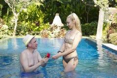 在水池的爱恋的夫妇在有热带树的一个庭院里 人拥抱妇女 免版税库存图片