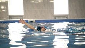 在水池的美好的专业游泳者游泳仰泳,照相机移动式摄影车射击 库存照片