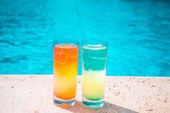 在水池的背景的两个五颜六色的热带鸡尾酒 异乎寻常的夏天休假 图库摄影