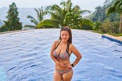 在水池附近的亚洲女孩身分在山 免版税库存图片