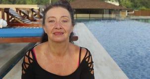 在水池附近的可爱的微笑的成熟妇女 股票视频