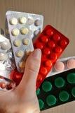 在水泡和片剂的黄色,红色,桃红色和橙色药片包装的组装,在手中举行,片剂 免版税库存图片