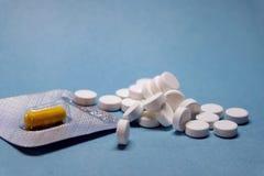 在水泡的黄色胶囊药片和白色圆的药片散装在蓝色背景的 免版税库存照片