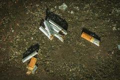 在水泥地板上的烟头 免版税库存图片