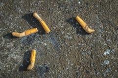 在水泥地板上的烟头 库存照片