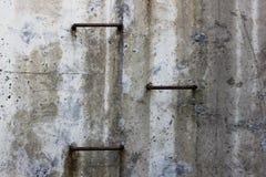 在水泥灰色墙壁上的三金属步导致地球的表面从隧道 免版税库存照片