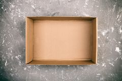 在水泥灰色背景葡萄酒,被定调子的,顶视图的被打开的棕色空白的纸板箱 免版税库存照片