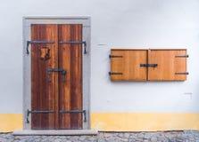 在水泥白色墙壁上的老木双门有小木的 库存照片