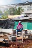 在水泥的妇女建筑工人等待的石膏工灰浆,曼谷泰国2月10日18日 库存照片