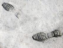 在水泥路的脚印鞋子 免版税库存照片
