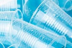 在水滴的空的透明一次性塑料玻璃在明亮的蓝色背景的 图库摄影