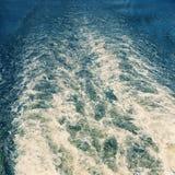 在水的一串美丽的足迹从船在一个清楚的夏日 背景 免版税库存照片