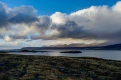 在水的冰岛视图往与蓝天和clou的山 免版税库存图片