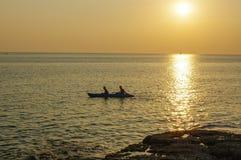 在水的惊人的热带橙色日落,与岩石剪影和一条小船在普吉岛海岛上,泰国 库存照片